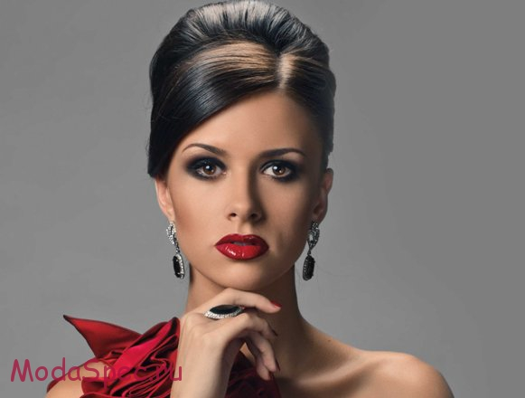 portrait of beautiful girl with elegant coiffure and red dress on grey
